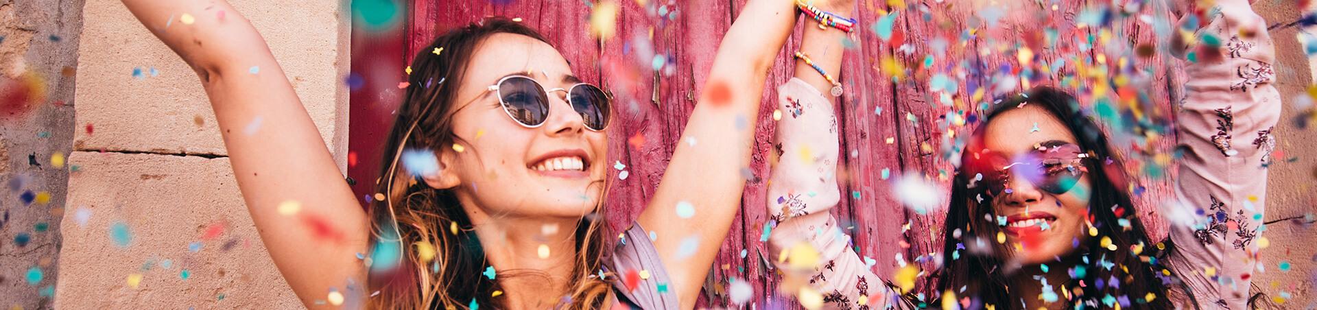 two women smiling while confetti falls around them