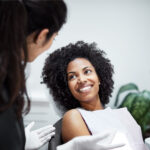 Curly haired woman at the dentist in the dental chair smiles after finding the best dentist in Canton, GA